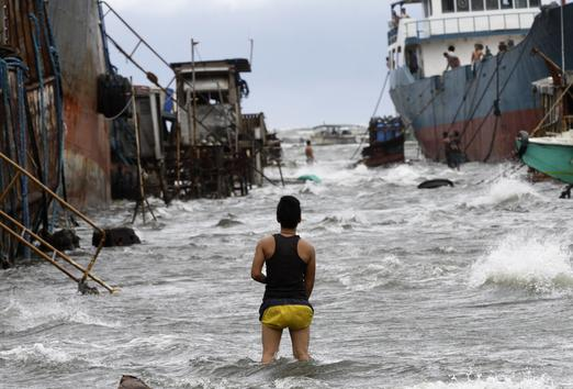 A man wades out on a submerged pier as tropical storm Mawar hits near suburban Navotas City northwest of Manila, Philippines on 2 June 2012. AP