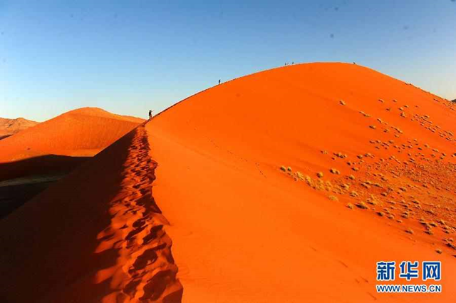 Tourists walk the red sand dunes of Sossuslvei desert park in Southern Namibia, 9 April 2012. In the summer of 2013, an estimated 778,000 Namibians, which equates to a third of the country's population, are either severely or moderately food insecure due to the worst drought in years. Photo: Xinhua