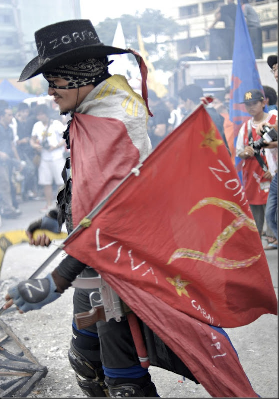 A colorful character wears the Philippine flag in one of the rallies against the sitting heads of the government.