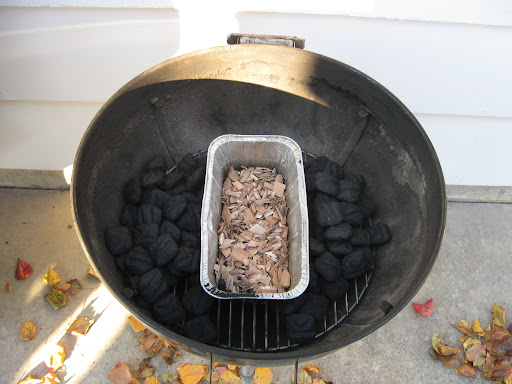 We use a Weber charcoal grill. An aluminum pan is set in middle of the bottom grill rack and filled with wood chips and water. Charcoal is then mounded on both sides of the pan.