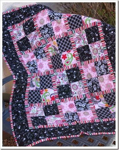 pink and black baby quilt with striped sashing