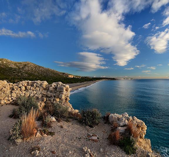 Restes d'una antiga torre de vigilància del segle XVI situada sobre l'illot del Torn. Al fons, la platja del Torn (platja nudista). Espai d'Interés Natural la Rojala platja del Torn. Hospitalet de l'Infant i Vandellòs, Baix Camp, Tarragona