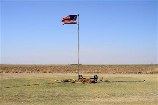 An frayed American flag stands sentinel over the harsh Texas Panhandle landscape and Lucas Spinhirne's farm southwest of Vega, Texas. The tattered edge is a testament to the relentless wind in the Panhandle. Photo: Gil Aegerter / NBC News