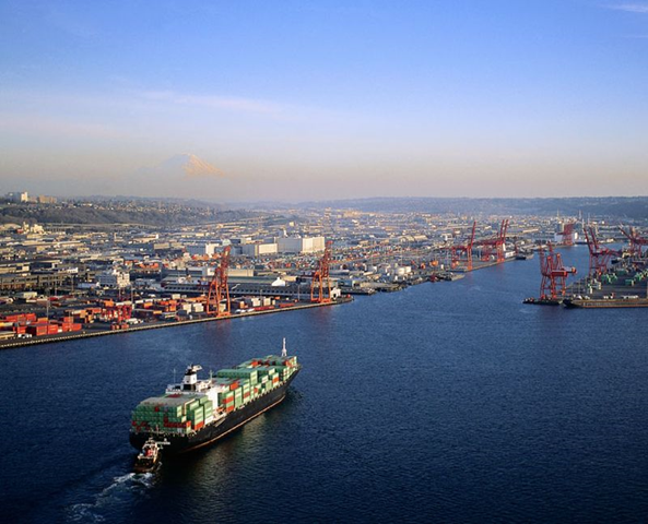 Aerial view of a cargo ship entering the Port of Seattle. Mount Rainier is visible on the horizon. Corbis