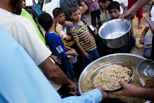 Syrian refugees wait to receive food from a makeshift kitchen in a temporary refugee camp near the Al-Salama crossing between Syrian and Turkey on September 8, 2012. Fighting for control of a key army base in Aleppo raged, as Russia tried to revive a divisive accord on ending the bloodshed that calls for a government of unity in Syria. AFP PHOTO/ACHILLEAS ZAVALLIS