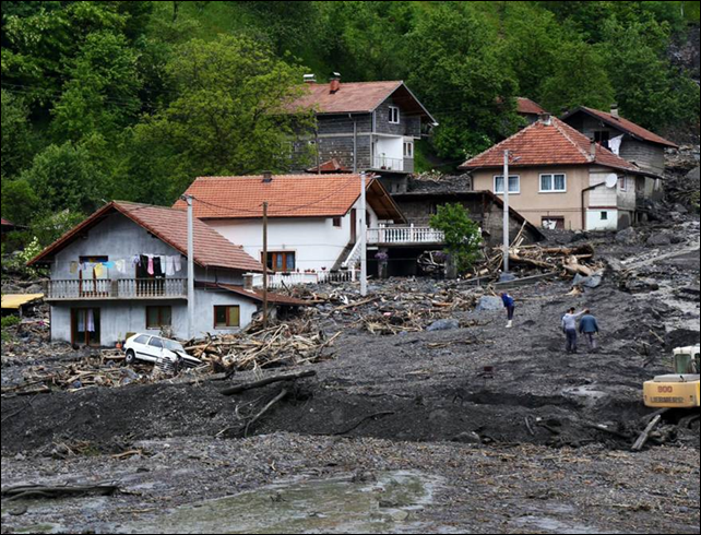 Houses sit damaged from record-breaking rains in Sarajevo, Bosnia, and Herzegovina on 17 May 2014. Throughout hilly Bosnia, floods triggered landslides covering roads, homes, and whole villages. Photo: Ismail Duru / Anadolu / Getty Images