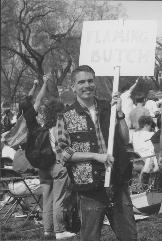 "Man holding a ""Flaming Butch"" sign at the March on Washington. 1993."