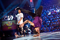 Lil G (R) of Venezuela performs as Morris (L) of the USA watches on during the Red Bull BC One breakdancing world finals at the Circus Nikulin in Moscow, Russian Federation on November 26, 2011.