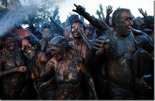 "Mud-covered revelers get sprayed with water during the ""Bloco da Lama,"" or ""Mud Block"" carnival parade in Parati. (Felipe Dana/Associated Press)"