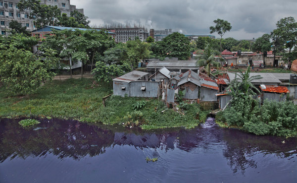 In Savar, an industrial suburb of Dhaka, Bangladesh, and the site of the deadly Rana Plaza building collapse, many factories do not treat their wastewater, as the purple canal makes clear. The building to the left partly hidden by trees is an elementary school, where the stench of the water sometimes makes the students ill. Photo: Khaled Hasan / The New York Times
