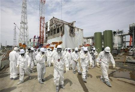 Members of the media and Tokyo Electric Power Co. (TEPCO) employees, wearing protective suits and masks, walk in front of the No. 4 reactor building at the tsunami-crippled Fukushima Daiichi nuclear power plant in Fukushima prefecture 26 May 2012. Tomohiro Ohsumi / REUTERS