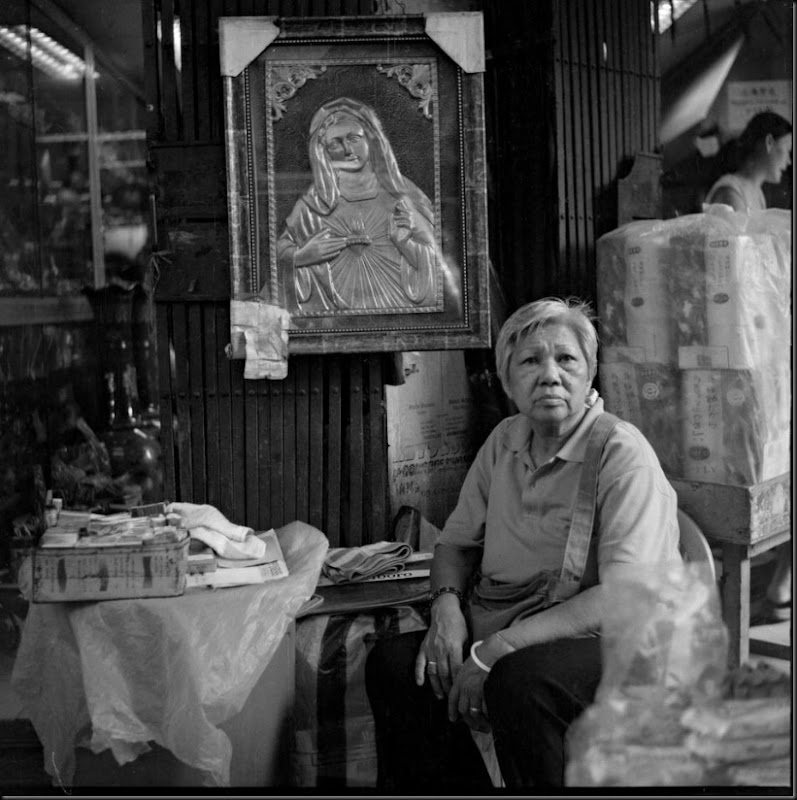 Portrait of a street vendor selling cigarettes and a large religious item on the streets of Manila.