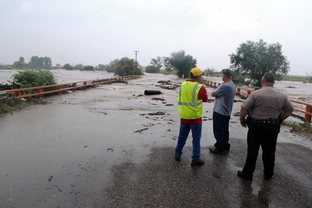 Observers from the Chaves County Sheriff's Department and the City of Roswell watch as Berrendo Creek begins to spill over the N. Red Bridge Road bridge in Roswell, New Mexico, Wednesday, 11 September 2013. Photo: Mark Wilson / Roswell Daily Record