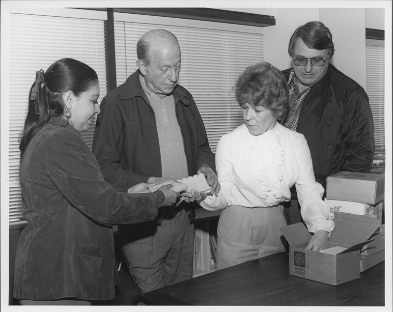 W. Dorr Legg accepts on behalf of ONE Incorporated 1 million dollars in gold krugerands to purchase the Milbank Estate on Country Club Drive in Los Angeles. The gold was donated by Reed Erickson. Circa 1983.