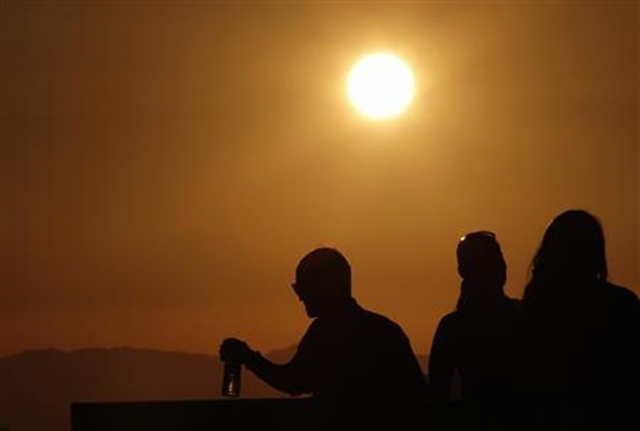 The sun shines on people standing on the roof observation deck of the Griffith Observatory, as a potentially dangerous heat wave grips the western U.S., in Los Angeles, California, 29 June 2013. Photo: Jonathan Alcorn / REUTERS
