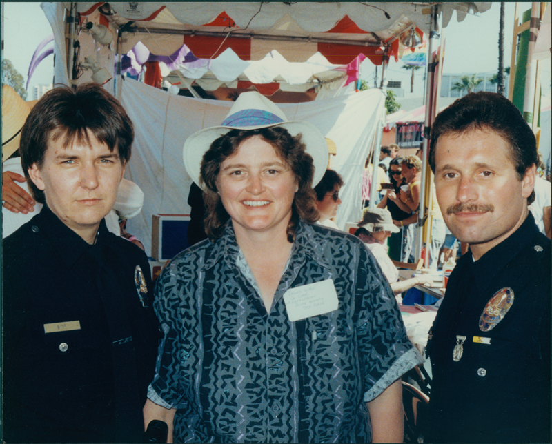 Donna Wade, co-chairperson of the Los Angeles Gay and Lesbian Police Advisory Task Force, with two police officers at the Sunset Junction Fair. Circa 1989-1990.