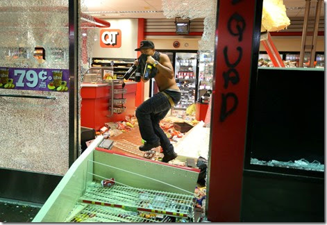 A looter takes items from inside the QuikTrip in 9400 block of W. Florissant Avenue in Ferguson, Mo. on Sunday, Aug. 10, 2014..  The looters later burned the store.
