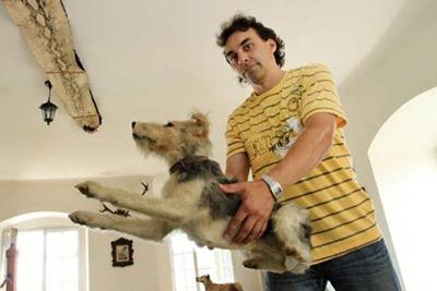 Kan Bider, diretor do castelo, segura um cão da coleção. (Foto: Radek Mica/AFP)