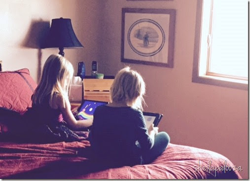 cousins on bed with ipads