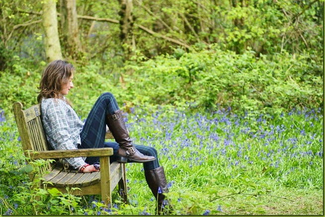 girl on bench in bluebells