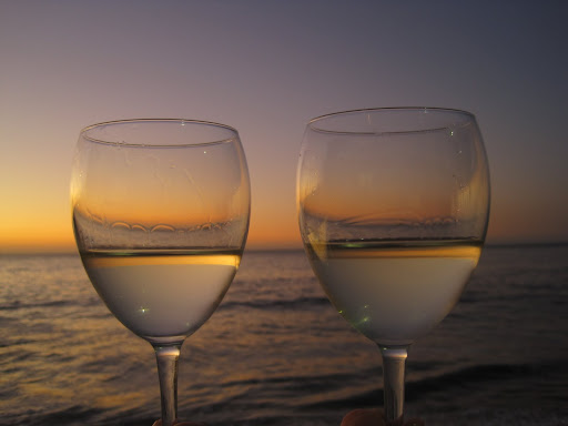 Enjoying a beautiful sunset with some beachfront wine.