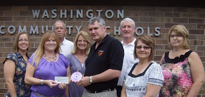 Agents pictured: Left to right, Heather Lujano, Charla Howard (presenting check), Tim Zear, Cheryl Kurtz, Dr Mike Jorgensen (accepting the check), Myron Graber, Connie Larsen and Rhonda Wilson.  Photo Courtesy:  Charla Howard