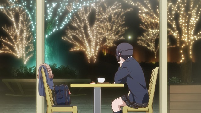 A horizontal shot of Iori sitting alone at night at a cafe table with tea and her coat and bag on the chair across from her as she looks out big windows at trees lined with lights