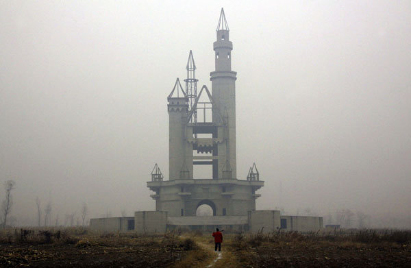 The unfinished replica of the tower at the entrance to Disneyland rises from empty fields in China's abandoned fake Disneyland, 14 December 2011. David Gray / Reuters