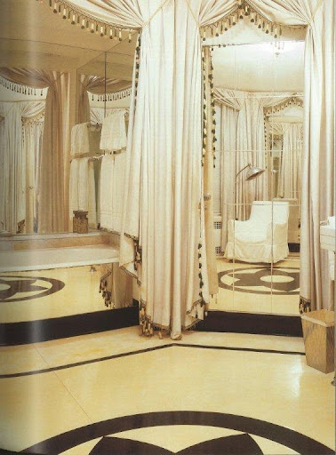 This bathroom is so luxe with it's mirrored and curtain-framed walls and bathtub, marble floors, and a club chair to lounge in underneath a hair-drier.