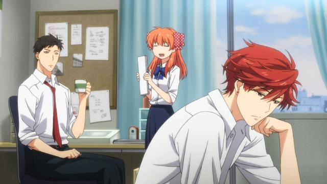 Nozaki sits at his drawing desk at home calmly holding a cup as Chiyo stands before him holding some manuscripts. In the foreground, Mikoshiba is sitting bored, hand on chin, at the table in the middle of the room.