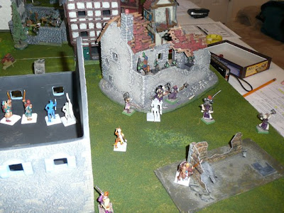 Heroes charging a ruined house under goblin fire
