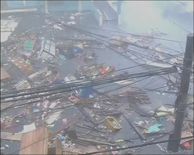 Debris float on a flooded road as strong winds and rain continue to batter buildings after Typhoon Haiyan hit Tacloban city, Leyte province in this still image from video, 8 November 2013. Photo: REUTERS / ABS-CBN via Reuters TV