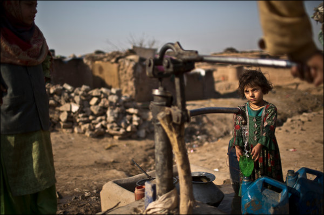 Afghan refugees pumped water by hand in a slum of Islamabad, Pakistan. An official warned that Pakistan could become 'a water-starved country'. Photo: Muhammed Muheisen / Associated Press