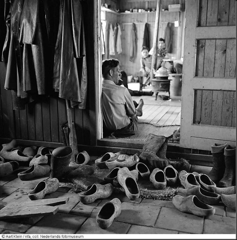 Klompen, jassen en laarzen zijn achtergelaten bij de ingang van een arbeidersbarak, 1e werkkamp (bouw Haringvlietdam) te Hellevoetsluis (1957)