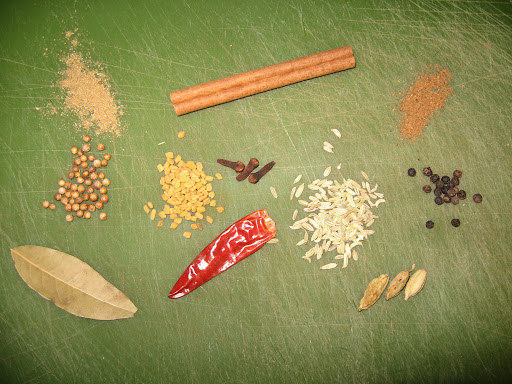 These are some of the spices we used (from left): ground and whole coriander, bay leaves, cinnamon stick, fenugreek seeds, cloves, dried hot Indian chiles, fennel seeds, garam masala, peppercorns, and cardamom pods.