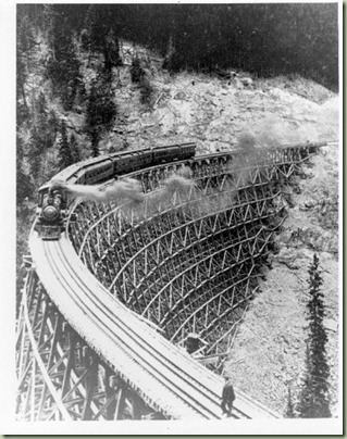 Kettle Valley Railway timber trestle at MP87.9. Replaced with steel structure 1932. Eastbound passenger train. Circa 1915.