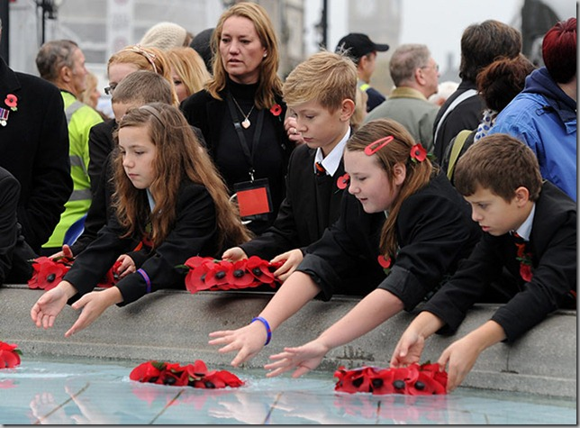 Children-place-poppies-in Trafalgar Square fountain