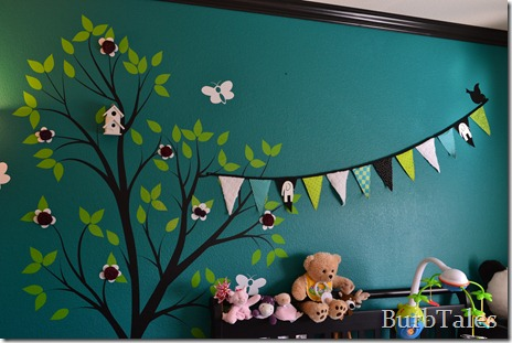 Teal nursery with tree and fabric flowers