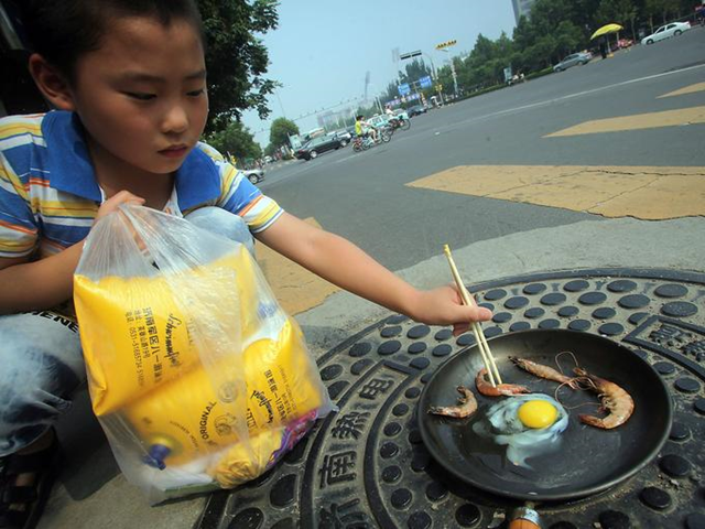 A child cooks shrimp and an egg in a frying pan heated by a manhole cover on a hot summer day on 31 July 2013 in Jinan, China. It has been so hot that eggs are hatching without incubators and a highway billboard burst into flames in the worst heat wave in at least 140 years. Photo: China Daily / AP