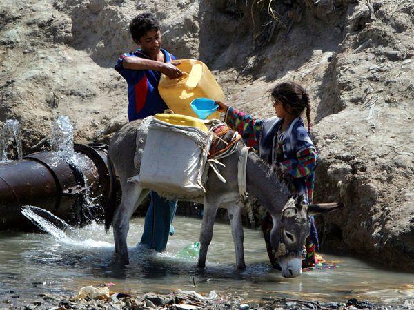 Children gather water from a broken pipe in Baghdad's Sadr City. Karim Kadim / AP