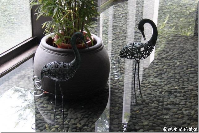 一樓樓梯下的水景裝飾藝術,有兩隻黑天鵝站在水面上。
