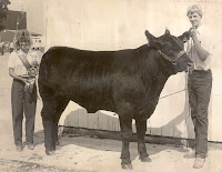 "1983 Beef Queen Deb (Bohr) Vittetoe stands with champion beef showman, Dave Richardson.  Vittetoe was a member of the 4-H Maidens from 1975-1883.  She explained, ""One valuable skill I learned [in 4-H] and use today is sewing.  Even though most do not sew clothing like they used to years ago, I use my sewing skills often fixing zippers, sewing buttons, hemming pants, etc.  I am so glad my mom took the time and patience to teach us four girls those skills.""   Vittetoe has had three of her own children go through the 4-H program as well and enjoys seeing former 4-H friends from years back at the fair each year.  Photo Courtesy:  Washington County Extension."