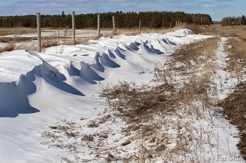Snow drifts along the road