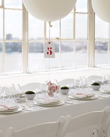 To make these whimsical table numbers, tie oversized helium balloons with baker's twine to small rocks wrapped in fabric. Then, paint numbers onto hang tags using stencils from a hardware store, and tie in place on the twine.