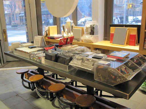 A table in the front of the store has many small accessories from wallets to color pencils, to key chains and notebooks. I love the swinging stools below the table.