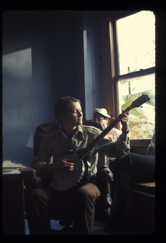 Brenda Weathers playing her banjo at the Alcoholism Center for Women, behind her is Dottie Howard, the first ACW recovery house manager. Circa 1975