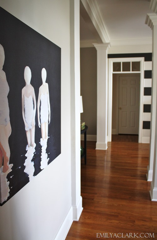 artwork in hallway with striped foyer
