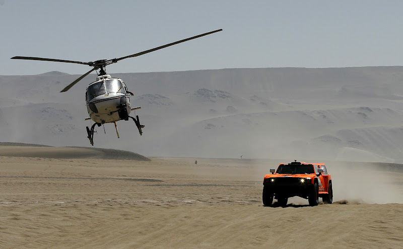 A helicopter flies overhead as hummer driver Robby Gordon and co-driver Johnny Campbell, both from the U.S., compete in the 13th stage of the 2012 Argentina-Chile-Peru Dakar Rally between Nazca and Pisco, Peru, Saturday Jan. 14, 2012. (AP Photo/Martin Mejia)