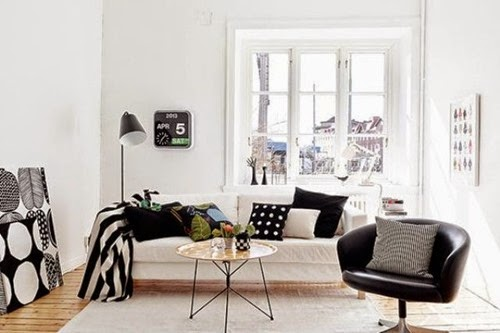 wooden-floor-floor-lamp-grey-rug-black-arm-chair-glass-window-white-sofa-with-cushions-duvet-rounded-coffee-table-ornaments