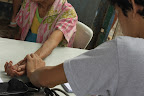 A volunteer medical student takes the vital signs of an old woman. (Photo by RVO/Bulatlat.com)